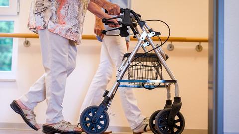 Eine Pflegekraft geht mit einer älteren Dame über einen Korridor.
