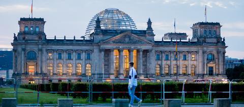 Ein Passant geht morgens am Reichstagsgebäude vorbei.