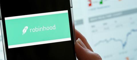 Auf dem Handy leuchtet das Logo der Trading-App Robinhood auf.