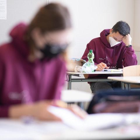 Jugendliche sitzen mit FFP2-Maske bei einer Abitur-Klausur in der Schule