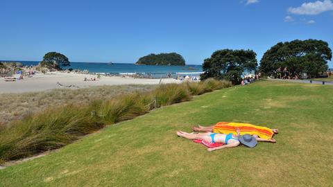 Symbolbild: Sonnanbeter liegen am Strand in Neuseeland
