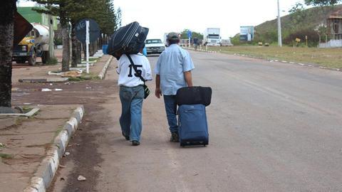 Zwei venezolanische Flüchtlinge tragen ihre Koffer über die brasilianische Grenze.