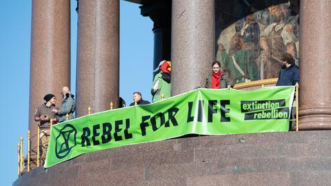 """Demonstranten der Protestbewegung """"Extinction Rebellion"""" halten ein grünes Banner hoch mit der Aufschrift """"Rebel for Life"""""""