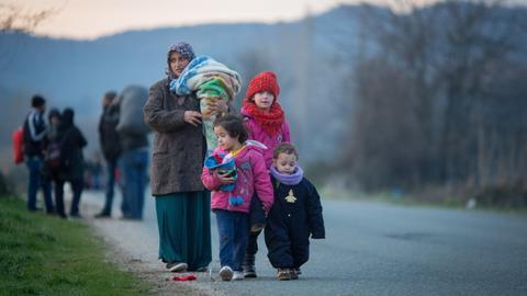 Flüchtlinge laufen auf einer Straße zum Flüchtlingslager in Idomeni