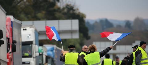 Demonstranten in gelben Westen schwingen französische Fahnen auf der Autobahn