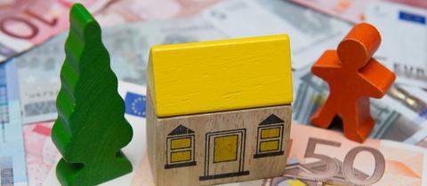 Ein kleines Spielzeughaus steht am 09.09.2010 in Sieversdorf (Brandenburg) auf Geldscheinen.