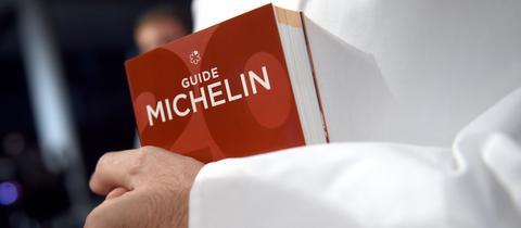 Ein Koch hält den Guide Michelin im Arm