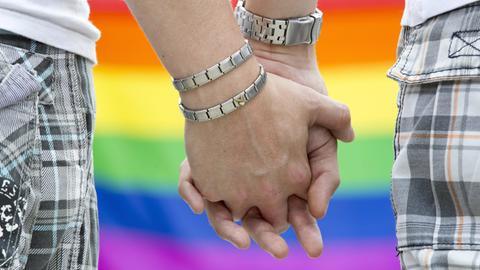 Zwei Männer, die vor einer Regenbogen-Flagge Händchen halten