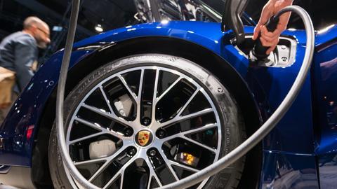 Das Rad eines blauen Porsche Taycan Turbo und eine Hand, die das Ladekabel des Autos hält