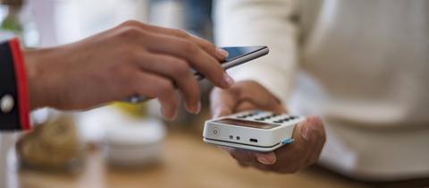 Ein Kunde bezahlt in einem Geschäft mit seinem Handy .
