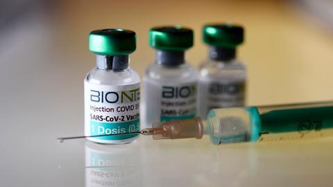 Drei Fläschchen Corona-Impfstoff der Firma Biontech stehen auf einem Tisch, davor liegt eine Nadel.