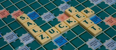 """Auf einem Scrabblespiel liegen die Worte """"Salz"""", """"Zucker"""" und """"Fett""""."""
