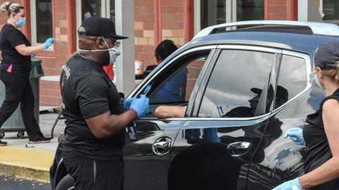 """Mitarbeiter einer """"Drive-Thru""""-Impfstelle in Orlando, Florida, verabreichen Menschen eine Dosis mit dem Corona-Impfstoff von Johnson & Johnson"""