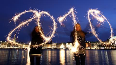 """Zwei Mädchen """"schreiben"""" mit Wunderkerzen die Jahreszahl 2010"""