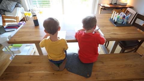 Zwei Kinder sitzen zu Hause an einem Tisch und machen Schulaufgaben.