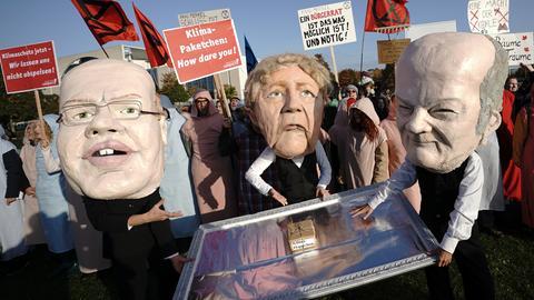 Aktivisten von Campact mit Masken von Wirtschaftsminister Altmaier, Kanzlerin Merkel und Finanzminister Scholz zeigen mit einem kleinen Klimapaket auf einem Silbertablett während der Sitzung des Bundeskabinetts vor dem Kanzleramt.