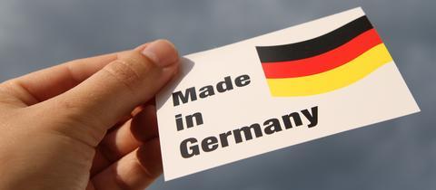 """Eine Hand hält ein Schild in die Luft mit der Aufschrift """"Made in Germany"""""""