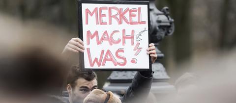 """Schild mit der Aufschrift """"Merkel, mach was!"""""""