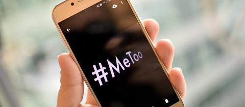 """Eine junge Frau hält ein Smartphone mit dem Hashtag """"#MeToo"""" in der Hand."""