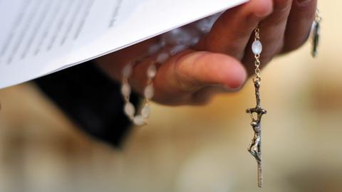 Ein Priester hält einen Rosenkranz und eine bischöfliche Erklärung zu den Missbrauchsfällen durch Jesuiten-Pater in der Hand