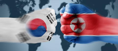Zwei Fäuste mit den Flaggen von Nord- und Südkorea