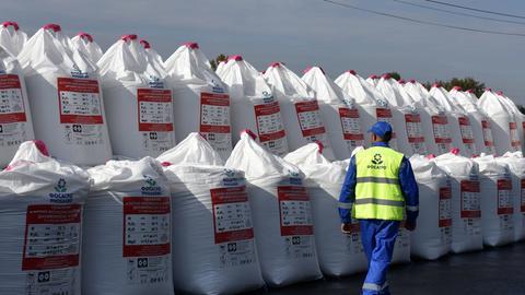 Säcke voller Phosphor gestapelt, ein Arbeiter läuft vorbei.
