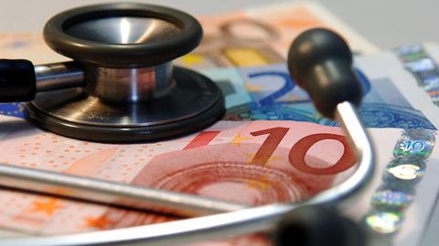 Ein Stethoskop liegt auf Euroscheinen