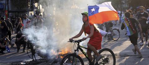Eine junge Frau auf einem Fahrrad bei Protesten in Chile