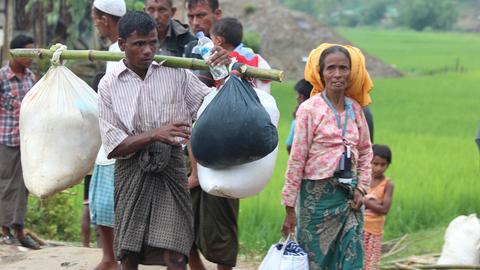 Zwei Rohingya-Flüchtlinge tragen ihr weniges Hab und Gut