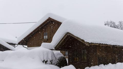 Tief verschneite Dächer von Holzhäusern