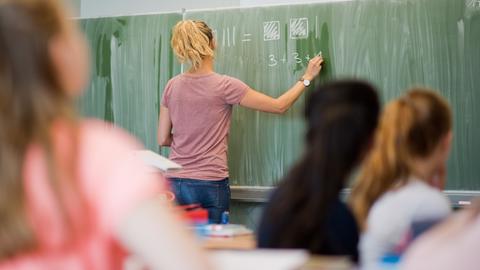 Lehrerin steht an einer Tafel in einem Klassenzimmer