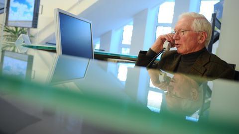 Ein älterer Herr sitzt am Empfang und telefoniert