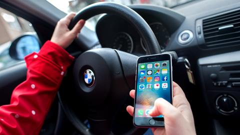 Ein Autofahrer schaut auf sein Smartphone