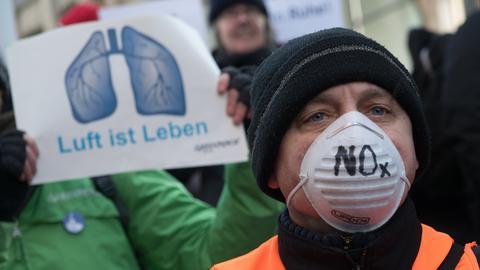 Greenpeace-Demonstrant mit weißer Atemschutzmaske auf der steht: NOX