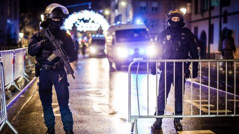 Polizisten stehen in Straßburg und riegeln nach eine Anschlag eine Straße  ab