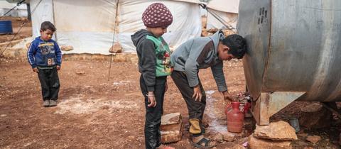 Syrische Kinder füllen Wasser aus einem Tank in eine Kanne in einem Flüchtlingslager für Binnenflüchtlinge in der Nähe des Dorfes Kafr Aruq.