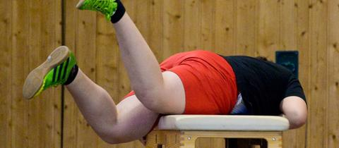 Ein übergewichtiges Kind beim Sportunterricht