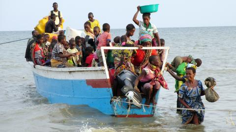 Ein kleines blaues Boot mit rund 30 kongolesischen Flüchtlingen kommt an der ugandischen Küste an