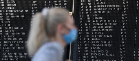 Eine Frau, die einen Mundschutz trägt, steht im Terminal 1 des Frankfurter Flughafens in der Abflughalle vor einer großen Anzeigetafel.