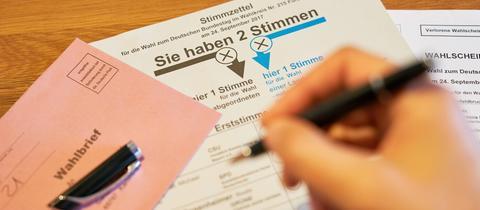 Eine Hand setzt zum Kreuz auf einem Wahlzettel an