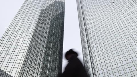 Ein Mann schaut die Deutsche Bank Türme in Frankfurt hoch