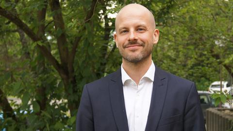 David Fuhr von der Firma HiSolutions vor einem grünen Baum