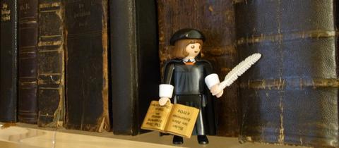 Eine Lutherfigur vor Lutherbibeln