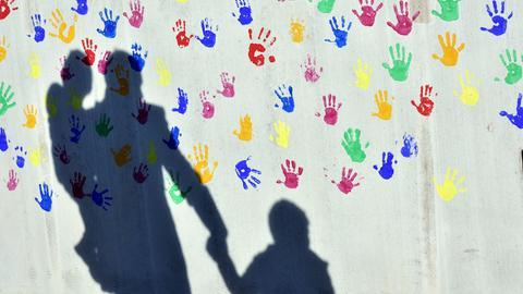 Schatten von einem Erwachsenen, der ein Kind an der Hand hält
