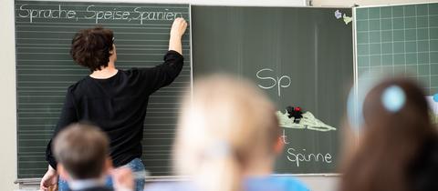 Lehrer steht an der Tafel