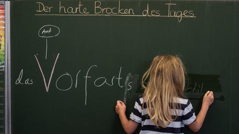 Kind steht vor einer Tafel und schreibt etwas an