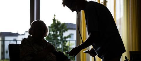 Eine Pflegerin misst in einem Heim einer älteren Dame den Blutdruck