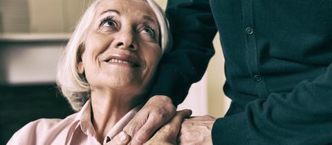 Eine ältere Frau schaut lächelnd nach oben zu einem Mann, der ihr die Hand auf die Schultern legt