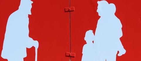 An einer roten Hauswand sieht man die weiße Silhouette eines Mannes am Gehstoch und ihm gegenüber ein Mann mit zwei Kindern