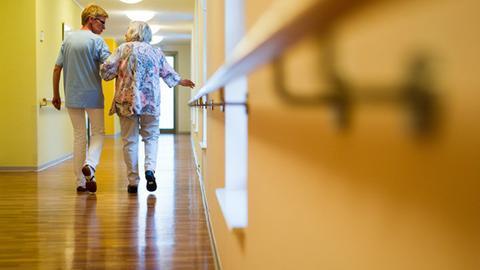 Eine Pflegerin läuft mit einer Pflegebedürftigen durch einen Gang